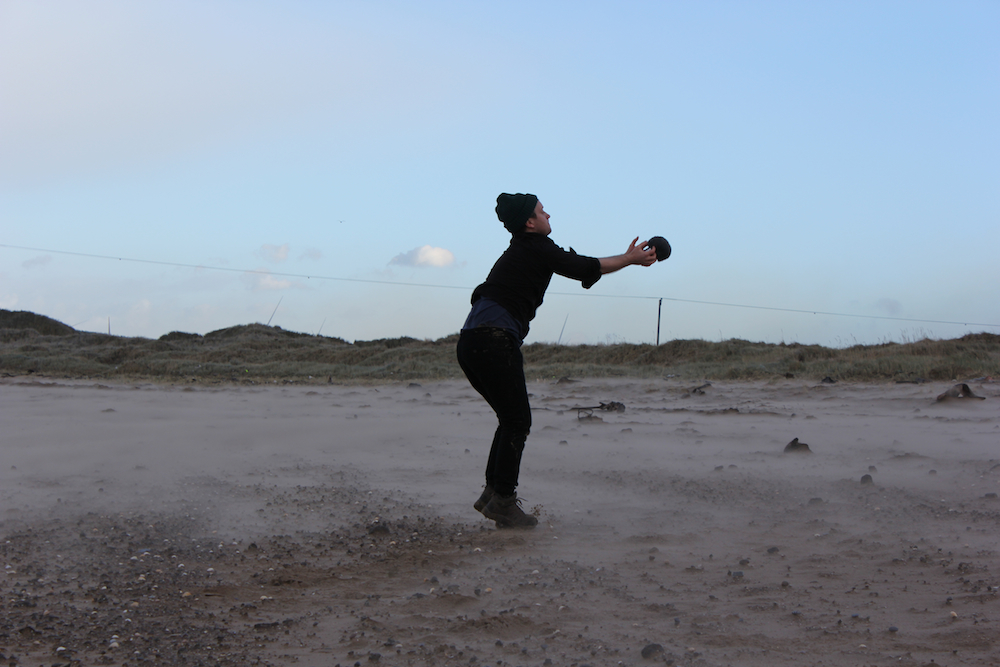 Mark Peter Wright is catching an object on a sandy beach.