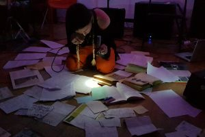 Brigitte Hart is performing by torchlight amongst amongst a spread of books and papers.