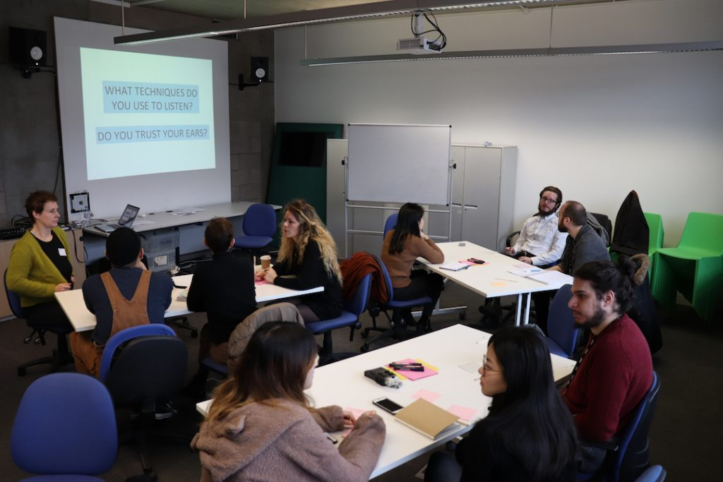Image shows students sat in groups discussing the questions: what techniques do you use to listen and do you trust your ears?