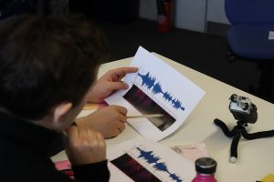Image shows students holding a spectrogram and discussing what they might hear in the image