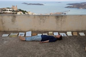 Brigitte Hart is lying on a concrete balcony listening to the sound of thirteen books in the wind.