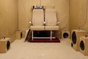 Image of an acoustic testing room featuring two airplane chairs and multiple speakers.