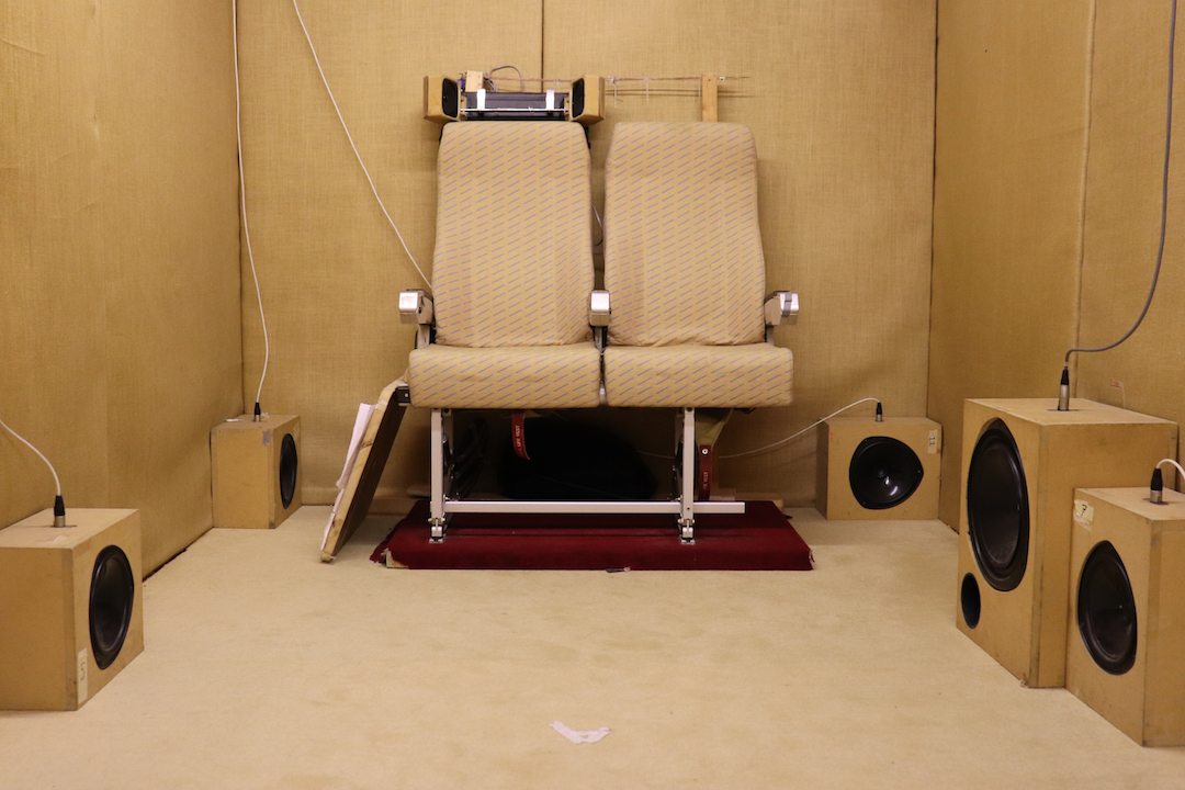 A small room with two airline chairs and multiple speakers which is used to test airport noise pollution.