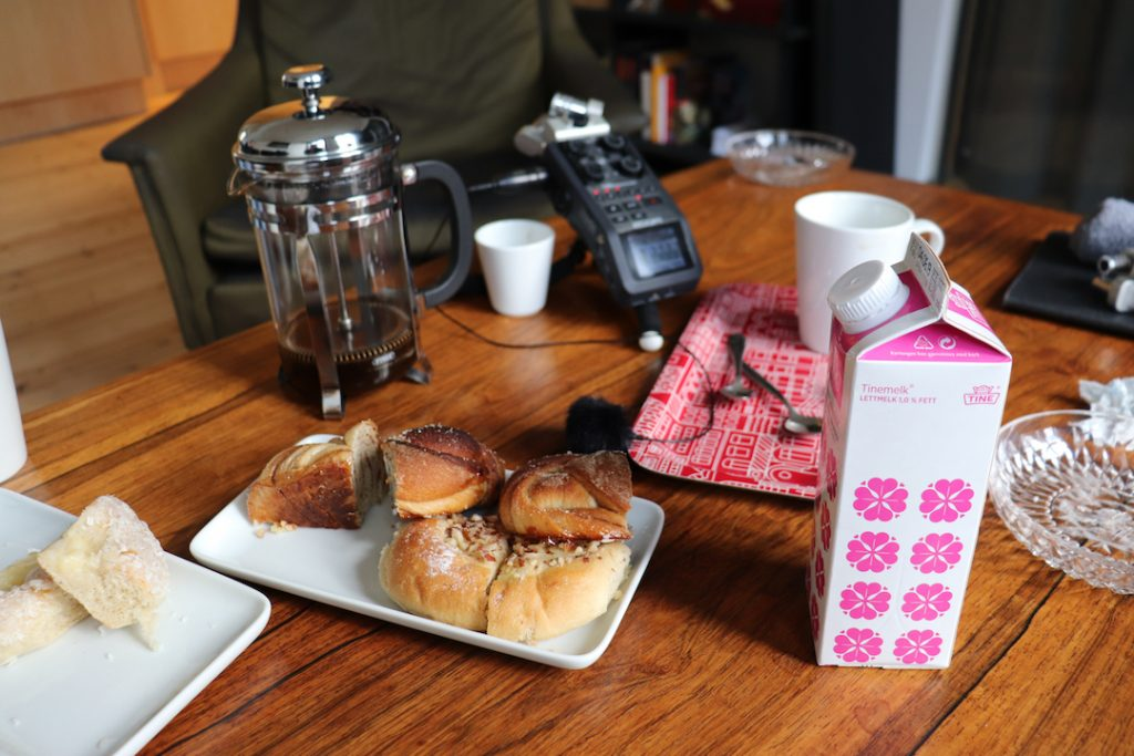 Image shows a table with a handheld recording device on it along with coffee and cake
